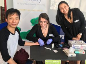 Otago pharmacy students Laura Pidcock (centre) and Nadine King offer a blood glucose test to Dunedin resident Van Chanusorn
