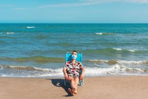 Man relaxing on a beach with mask